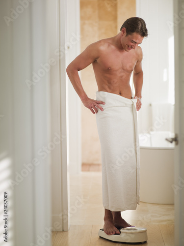 Man wrapped in a towel standing on bathroom scale with hands on hips ... 6b3b45110