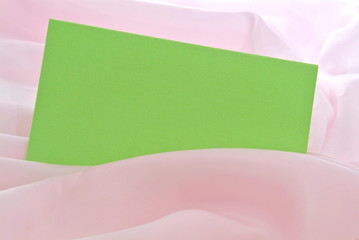 Eine grüne Karte in einem babyrosa Stoff. Sample text