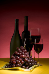 Red grape and wine bottle still life