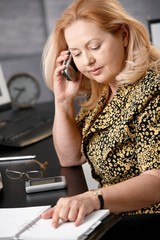 Senior woman on the phone at office