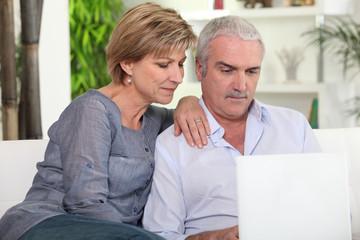 couple de seniors devant ordinateur portable
