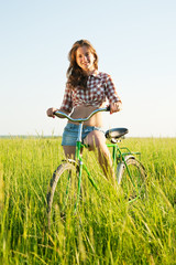Wall Murals Cycling girl riding bicycle in field