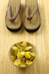 Wooden bowl of orchid with straw flip flops on mat