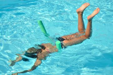 Femme qui nage en s'amusant dans la piscine