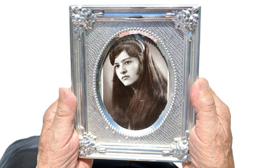 In youth. Mature woman holding old photograph