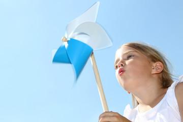 Obraz Closeup of little girl blowing blue wind wheel - fototapety do salonu