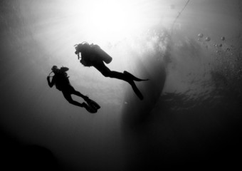 scuba divers silouetted by sun ball