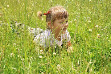 four years old girl lies in the grass - fototapety na wymiar
