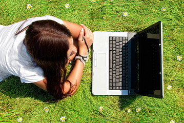Beauty on a grass with computer.