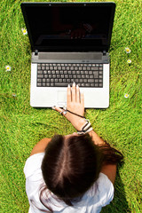Beauty on a grass with laptop.
