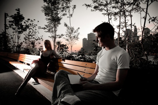 Young attractive couple sit next to each other on a park bench
