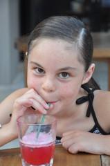 enfant fille qui bois un cocktail avec sa paille en été