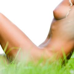 Beautiful nude woman sitting on grass