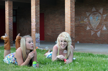 Two Girl Friends Blowing Bubbles in Grass