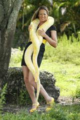 Young woman plays with an albino burmese python