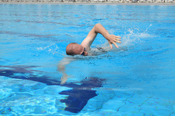 Young man swimming free style