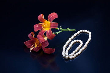 Lilies and a pearl necklace.