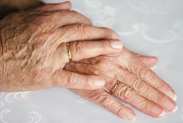 Zwei alte Hände mit Eheringen