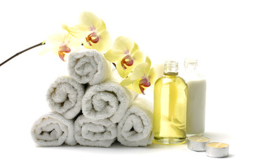 Rolled up white towel, candle, lotion with orchid