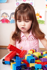 Child playing construction set in play room.