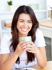 Beautiful asian woman holding a cup sitting in the kitchen
