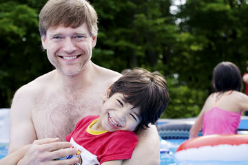 Father holding disabled son in pool