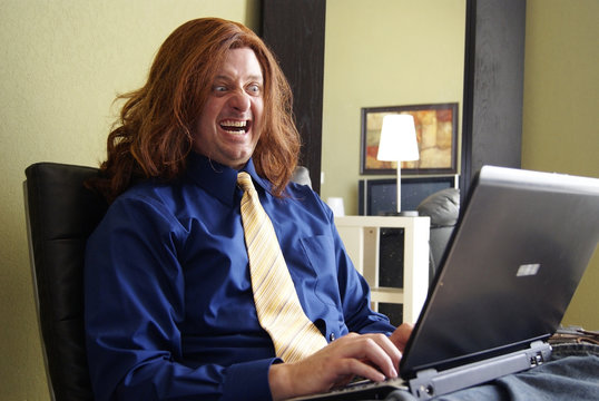 Silly Man with Long Hair on Laptop