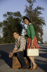 Boy and girl at roadside with suitcase