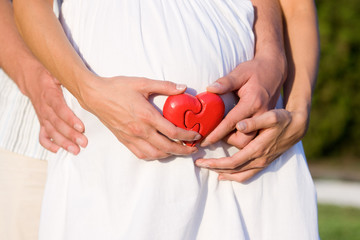 Belly of pregnant  with heart in hands