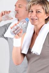 Homme et femme senior buvant de l'eau après le sport