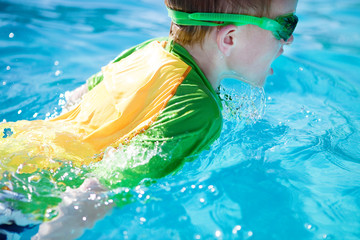 Young Boy Swimming in the Pool