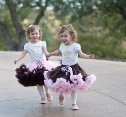 twin girl toddlers holding hands and laughing