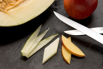 two blades, an apple, honeydew melon and slices of fruits