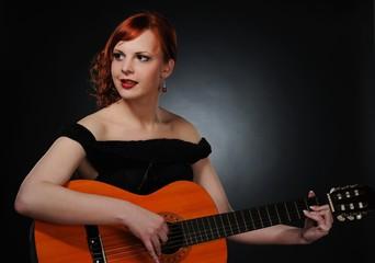 Beautiful redhead woman playing guitar