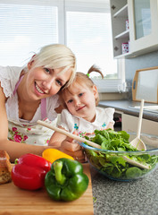 Smiling mother and daughter preparing a salad in kitchen
