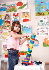 Child playing  block and construction set in play room.