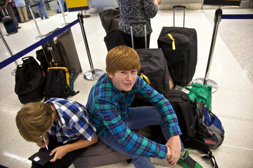 boys is sitting on the baggage waiting for check in