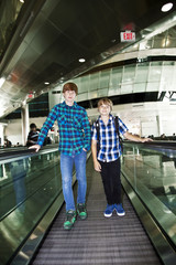 young boys on a moving staircase inside the airport