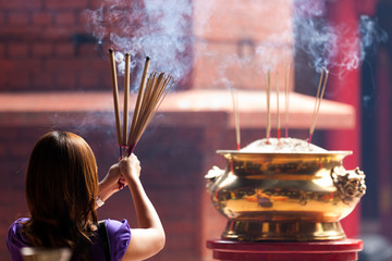woman holding incense sticks in chinese temple