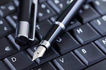 luxury black pen on computer keyboard