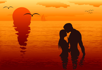 Lovers in the sea at sunset