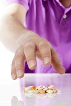 arzneimittelsucht - hand greift nach tabletten