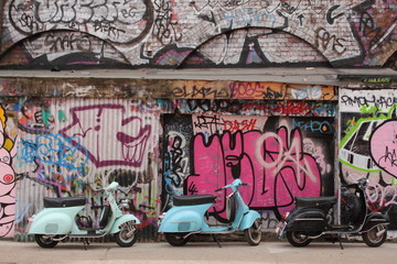 Three mopeds in front of graffiti