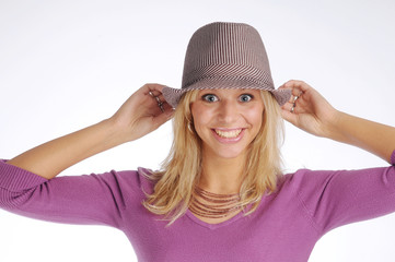 Atractive blonde woman with hat in violet sweater
