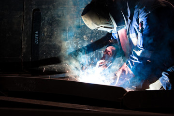 worker weld metal in factory and spark