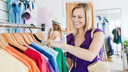 Delighted young woman choosing clothes