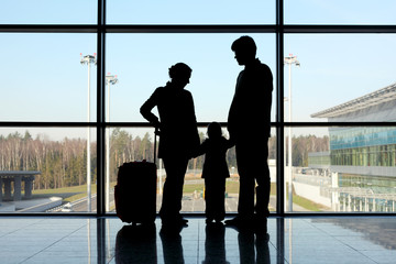silhouette of mother, father and daughter with luggage