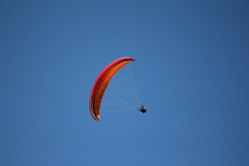 paragliding red and orange and sky blue