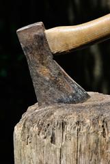 Old Lumberjack's Axe stuck in a chopping block closeup