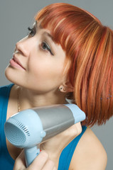 Woman with hairdryer and a hairbrush